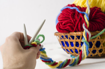 Hand holding knitting needles, colorful mixed yarn balls in background