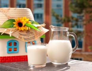 Молоко в кувшине и стакане на фоне игрушечного домика в соломенной шляпе. Домик создает деревенский стиль. Продукт стоит на балконе.