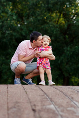 Dad with daughter on wooden bridge in park