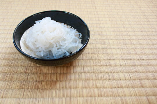 Shirataki noodles in black plate placed on Japanese traditional Tatami flooring mat