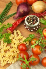 Raw pasta with tomatoes and parsley on a wooden background. Preparation diet food. The recipe for a simple dinner. Traditional pasta with vegetables.