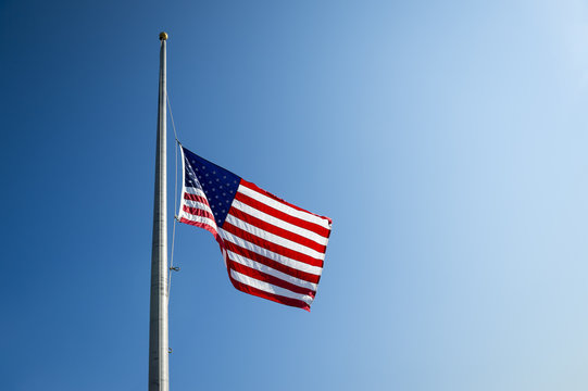 American flag flies at half mast backlit by the sun in bright blue sky
