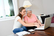 cheerful young woman giving computer lesson course to an elderly woman at home