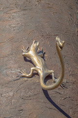 A detail of a modern monument with a golden lizzard or gecco