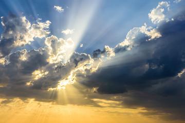 Sun beams breaking through the clouds at sunset. Beautiful