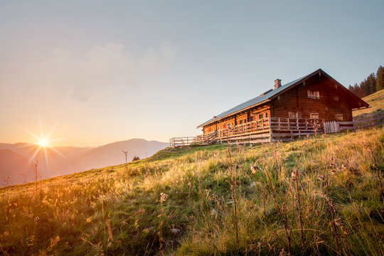 Wooden mountain hut at sunset in the alps in summer