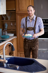 man in traditional bavarian clothes standing in kitchen