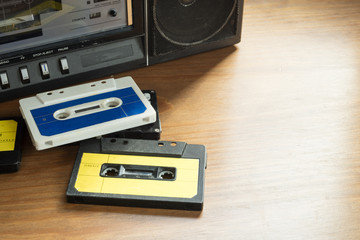 Vintage cassette tapes with radio-cassette player on a wooden table
