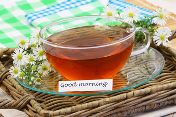 Good morning card with chamomile tea on wicker tray, closeup