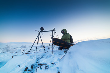 Man with photo camera on tripod taking timelapse photos in the arctic tundra.