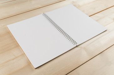 Open notebook with white  pages on wooden office desk .