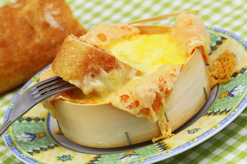 Piece of French bread dipped into baked cheese, close up