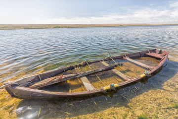 A sunken fishing boat full of water and seaweed.