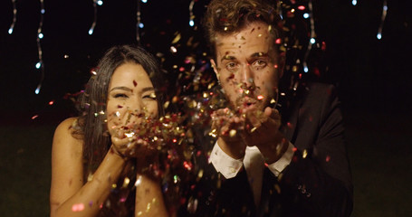 Young couple celebrating New Year blowing colorful paper confetti over their hands towards the camera against twinkling party lights