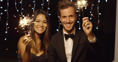 Elegant romantic young couple celebrating new year with sparklers laughing and smiling against a dark background with party lights