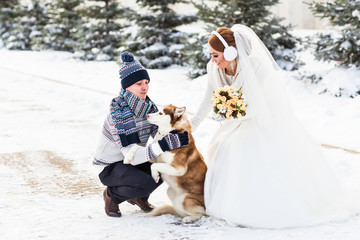 bride and groom with dog in winter