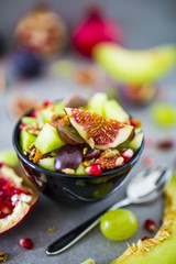 Delicious and healthy fresh fruit salad with figs, melon and pomegranate in bowl. Vegetarian food on grey stone background.