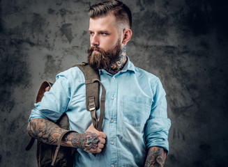 A man with tattoos on his arms and neck with backpack on his bac