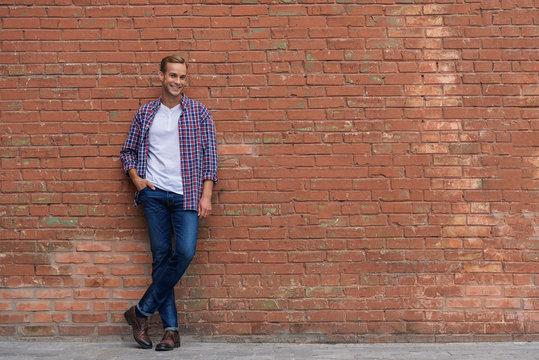 Handsome guy standing near brick wall