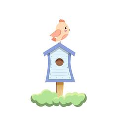 Bird sitting on birdhouse