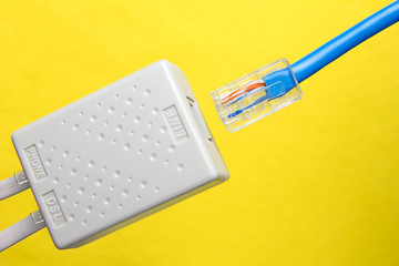 Twisted pair (patch cord) blue network Internet cable is inserted into the slot of the splitter on a yellow background. Top view.
