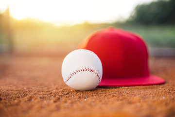 Baseball cap and ball on field