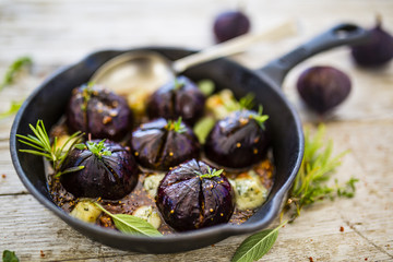 Oven-baked figs with gorgonzola, herbs and honey on frying pan with spoon.