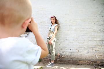 мальчик фотографирует девочку на фоне белой стены