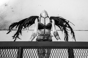 Top view black and white photo of beautiful seductive angel woman wearing lingerie and leather belts on the roof over white wall