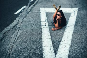Pretty brunette tourist girl sitting on the road