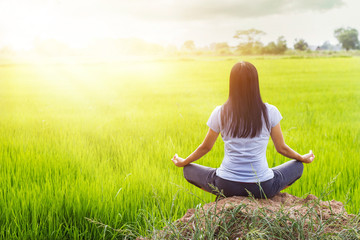 Meditating in the lotus posture on rice field background