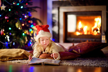 Adorable little girl reading a story book under a Christmas tree
