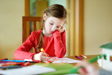 Cute little girl drawing a picture with colorful markers