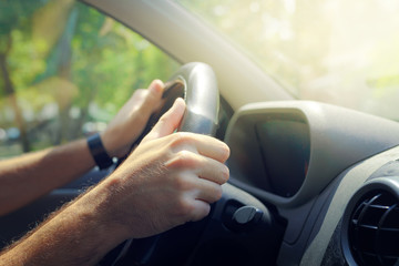 Male hands holding car steering wheel
