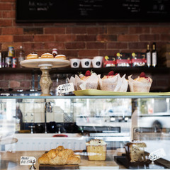 Cake display case in Melbourne cafe with rustic wall