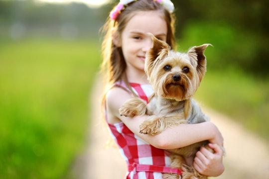 Cute little girl holding her yorkshire terrier dog