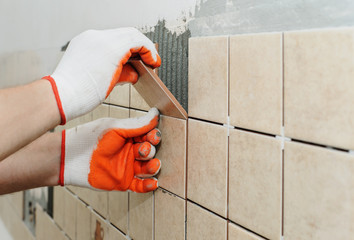 Obraz Worker  putting  tiles on the wall in the kitchen. - fototapety do salonu