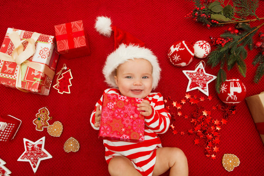Baby first christmas. Beautiful little baby celebrates Christmas. New Year's holidays. Baby with santa hat with gift. Santa baby.