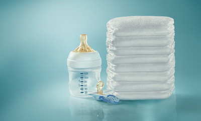 Stack of diapers. Baby bottle and pacifier. Studio Shot. Isolated