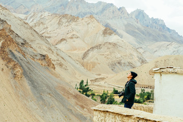 Asian travel photographer relaxing and breathing in mountain scene