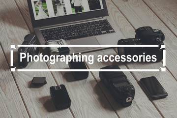 Photographing accessories and laptop on wooden background. Necessary tools for professional photographing lying near laptop with bundle of money