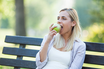 Young happy woman is sitting in park and eating apple.