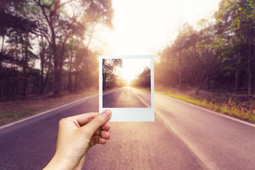 Hand holding photo frame empty asphalt road and sunset.