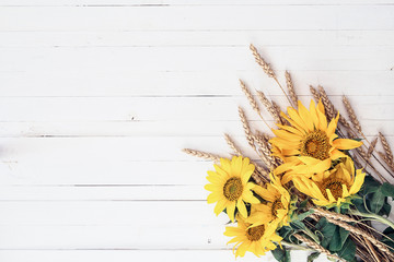 Background with a bouquet of yellow sunflowers and wheat ears on