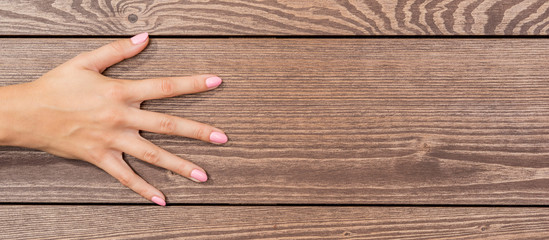 Female hand with pink nails on wooden table