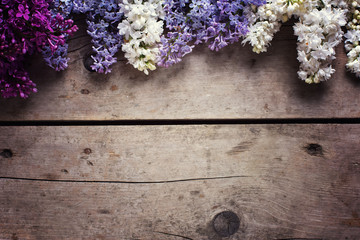 Border from aromatic lilac flowers on vintage wooden planks.
