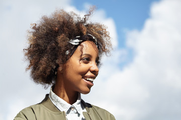 Headshot of beautiful dark-skinned young woman with Afro haircut wearing bandana and stylish clothes, relaxing outdoors, posing against blue sky background with copy space for your advertising content