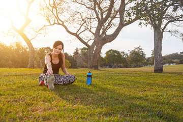 Young woman stretching her legs in a park in the sun