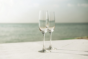 close up of two champagne glasses on beach