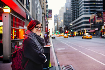 Side view of young woman waiting at sidewalk in city